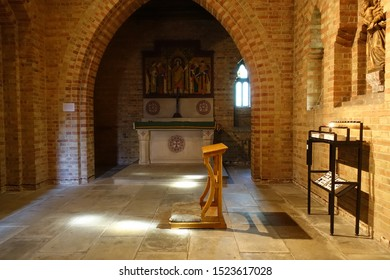Ryde Isle of Wight England October 2019. Quarr Abbey. Catholic Benedictine Order. Interior views of small atmospheric Pilgrim Chapel rear of Abbey. Altars, candle offerings, cross and domed tabernacle