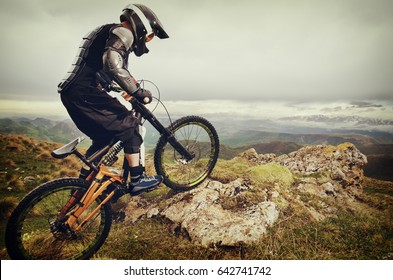 Ryder in full protective equipment on the mtb bike climbs on a rock against the backdrop of a mountain range and low clouds