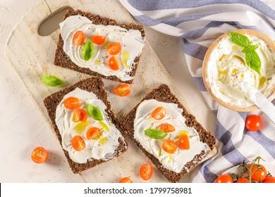 Brochetta de pain de seigle avec fromage à la crème, huile d'olive et trempette de basilic, tomates de cerise, feuilles de basilic fraîches sur planche de bois.