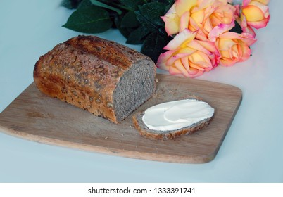 rye bread with butter on wooden board, rose on table