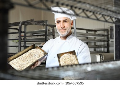 Rye bread. A handsome baker with a loaf of fresh bread standing in the bakery.