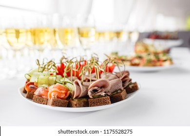 rye bread sandwiches, canapes, bruschetta on white plate. solemn banquet. Lot of glasses champagne or wine on the table in restaurant. buffet table with lots of delicious snacks.