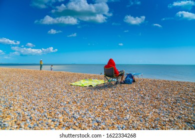 Rye England - August 20 2019; Man sitting in folding chair wearing bright red hoodie on stony beach.