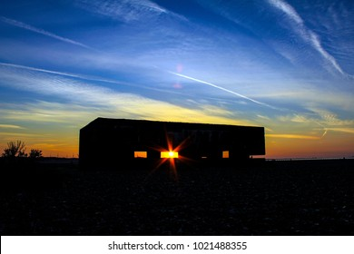 Rye Harbour blockhouse at dawn with sunrise shining through the emplacement window. This old building is on the Rye Harbour Nature and Bird Reserve near Rye, East Sussex, England.
