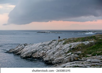 Rye, NH, USA - August 7, 2014: A Star Island visitor walks along the island cliffs as a sightseeing ferry takes shelter in the harbor during a summer storm.