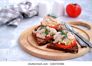 Rye open sandwich with tomato, egg salad and shrimps. Danish cuisine. Selective focus.