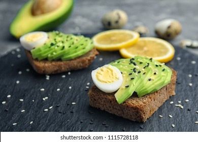 Rye toast with sliced avocado and quail eggs on slate plate, closeup