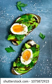 Rye toasts with soft cheese, avocado and boiled egg on a blue slate, stone or concrete background.Top view.