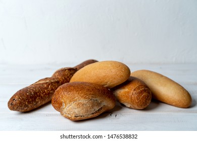 rye and wheat baguettes on white wooden table