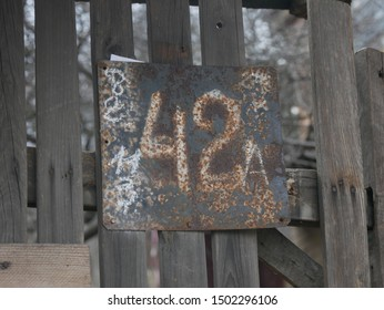 A rysty house number plate #42 on a wooden fence