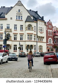 RZESZOW, POLAND- August 31, 2018: A woman biking on a cobbled stone street in the historical center of Rzeszow, Poland.