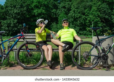 Rzeszow, Poland - Jun 23.2019  A young guy and a young girl are resting after a bike ride, drinking water, sitting on a bench. Outdoor activities. Two cyclists