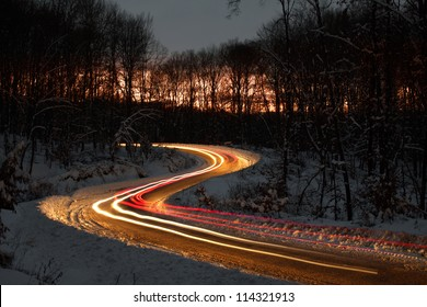 S curve on a forest road at night, just after sunset. The lights are created by the passing cars.