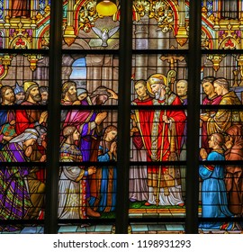 's Hertogenbosch, The Netherlands - July 23, 2011: Stained Glass in Den Bosch Cathedral depicting St Lambertus anointing the Taxandrians during the Confirmation, the rite of initiation in the Church
