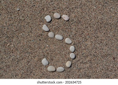 S letter made of stones on sand