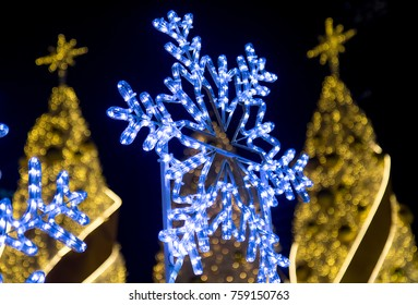 s neon lights in the shape of snowflakes shine before the golden decorated Christmas trees on the square in the night.