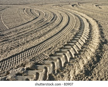 S shape tyre tracks on a beach in early morning light.