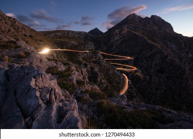 Sa Calobra road lit by the light of car at dusk, Mallorca island, Spain