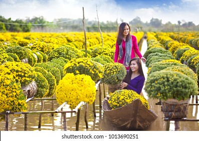Sa Dec Flower Village , Sa Dec town, Dong Thap province, Vietnam - January 23, 2018: Two young girl wearing Vietnamese traditional clothing (ao ba ba) on sampan, in yellow daisy floating farm