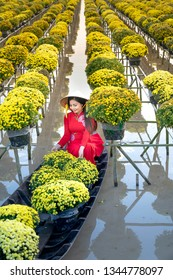 Sa Dec Flower Village , Sa Dec town, Dong Thap province, Vietnam - January 27, 2019: The young girls wearing Vietnamese traditional clothing (ao ba ba) on the sampan, in yellow daisy floating farm