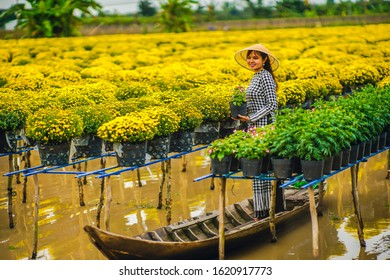 Sa Dec Flower Village , Sa Dec town, Dong Thap province, Vietnam - January 2, 2020: The young girls wearing Vietnamese traditional clothing (ao ba ba) on the sampan, in yellow daisy floating farm