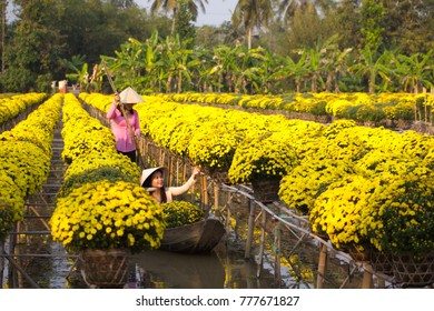 Sa Dec Flower Village , Sa Dec town, Dong Thap province, Vietnam - February 07, 2015: Young girls in sampan floating in yellow daisy country farm