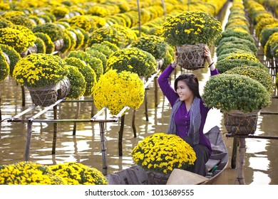 Sa Dec town, Dong Thap province, Vietnam - January 23, 2018: Young girl wearing Vietnamese traditional clothing (ao ba ba) holding flower pot, sitting on sampan, in yellow daisy floating farm