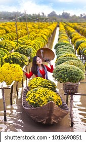 Sa Dec town, Dong Thap province, Vietnam - January 23, 2018: Young girl wearing Vietnamese traditional clothing (ao ba ba), holding conical hat, sitting on sampan, in yellow daisy floating farm