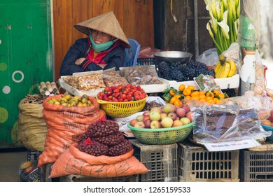 Sa Pa, Lao Cai, Vietnam - 11/26/2018:  Street vendor selling her fresh fruit and nuts and flowers in Sa Pa.