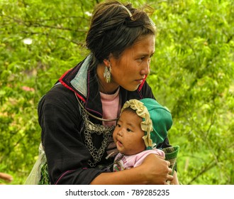 Sa Pa, Vietnam - July 1 2007: Hmong tribe woman in traditional black clothing hugging her young baby.