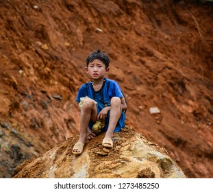 Sa Pa, Vietnam - May 31, 2016. A boy sitting on rock in Sa Pa, Vietnam. Sa Pa is a mountain town in Lao Cai, northwestern Vietnam.
