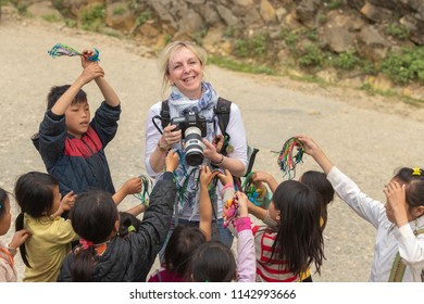 Sa Pa, Vietnam-April 14, 2018: European woman photographer among the children trying to sell local things and souvenir.