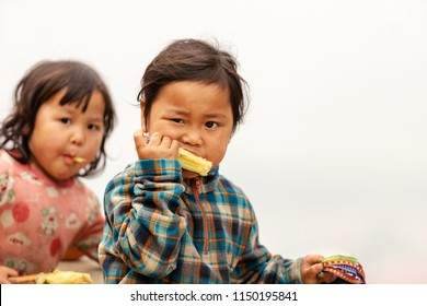 Sa Pa, Vietnam-April 14, 2018: Hmong child eating a piece of sugar cane in Sapa, North of Vietnam