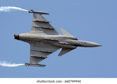 A Saab JAS 39 Gripen fighter jet flying with smoke trails.
