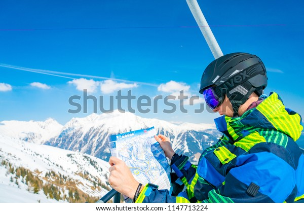 Saalbach, Austria. March 20, 2018. Young man riding up the ski lift exploring the map of the ski resort and slopes with an amazing view around him.