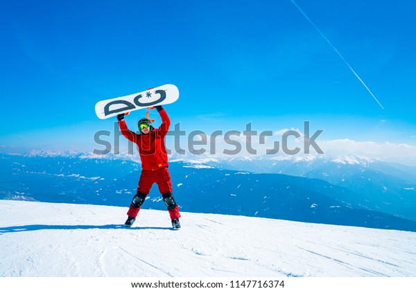 Saalbach, Austria. March 20, 2018. Young snowboarder standing on the top of the mountain with a snowboard. On top of the world. Success.
