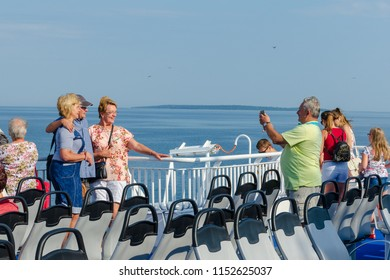 SAAREMAA, ESTONIA, July 14, 2018:  People on the ferry deck taking picture and departing from continent to Saaremaa