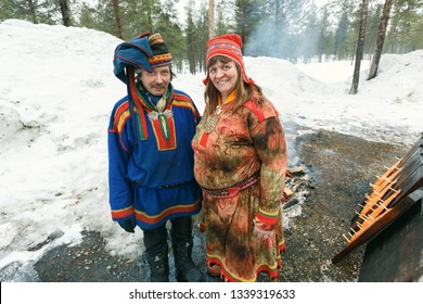 Saariselka, Finland - april 24, 2013: Local saami couple in a forest in front of a smoked salmon fillet prepared on fire in Saariselka, Finland