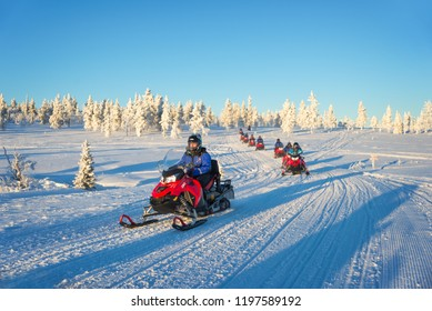 SAARISELKA, FINLAND - FEBRUARY 8: Group of tourists enjoying a ride with snowmobiles, in February 2, 2017 in Lapland, Finland