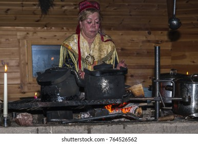 """Saariselka, Finland - November 29, 2010: Sami woman in traditional dress is cooking in a """"kota"""". The kota (also goahti), is a Sami hut with a fireplace in the center."""