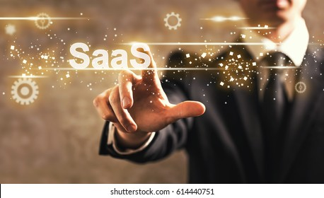 SaaS text with businessman on dark vintage background
