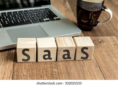 SAAS written on a wooden cube in front of a laptop