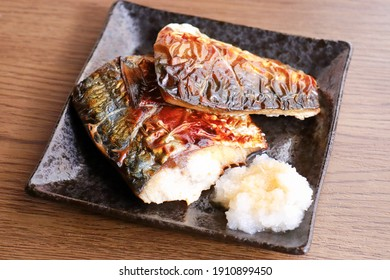 Saba no sio yaki (grilled mackerel). A traditional Japanese grilled fish dish. Two fillets on a black plate.