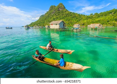 SABAH, MALAYSIA - APR 23, 2017: Unidentified Borneo Sea Gypsy kids on a canoes in Bodgaya Island in Tun Sakaran marine park, Sabah Borneo, Malaysia.