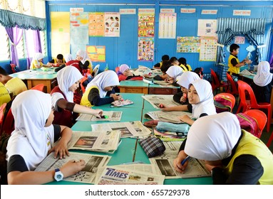 Sabah, Malaysia. April 10, 2017: Classroom of Malaysian primary school children in Kota Kinabalu having an English language lesson using local newspaper, Sabah Times, as learning materials.