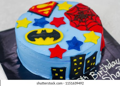Sabah, Malaysia, August, 3 2018 : Superhero inspired cake in blue color and superhero logo. Batman, Spiderman and superman. Kids Birthday Cake