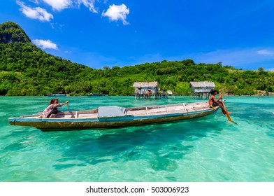 SABAH, MALAYSIA - JULY 6 2014: Bajau Laut kids on a boat in Bodgaya Island on July 6, 2014. They lived in a house built on stilts in the middle of sea, boat is the main transportation here.