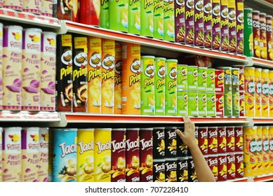 Sabah, Malaysia June 1, 2017: Hand reaching for Pringles potato chips at a supermarket. Potato chips are a favorite snacking food for many around the world