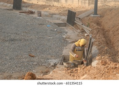 Sabah, Malaysia. March 3, 2017: Construction worker inspecting a drainage system for a shop lots building. Effective drainage system is curcial in all building construction.