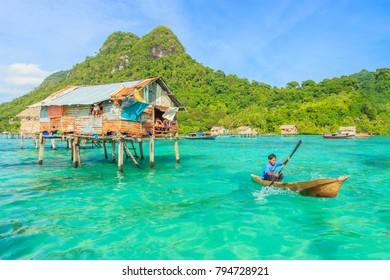 SABAH, MALAYSIA - OCT 18, 2017: Unidentified Borneo Sea Gypsy kids on a canoes in Bodgaya Island, Sabah Borneo, Malaysia.